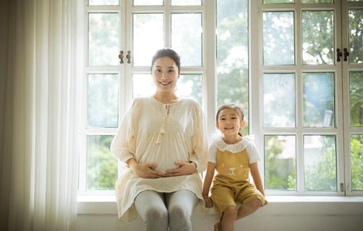 임신한 여성과 여저 아이가 나란히 앉아있는 모습