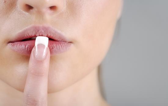 입술에 손가락을 데고 있는 여성
