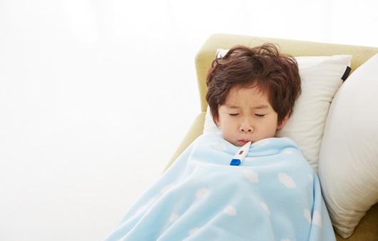 체온계를 물고 있는 감기에 걸린 아이