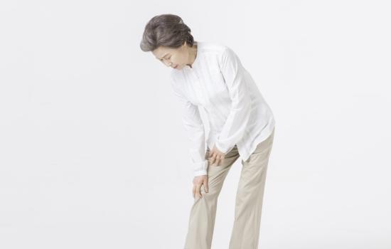 무릎에 통증을 느끼는 중년 여성