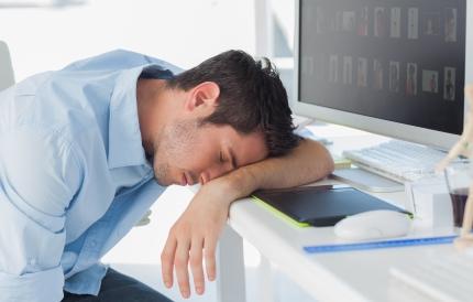 책상 앞에 엎드려 잠을 자고 있는 남성