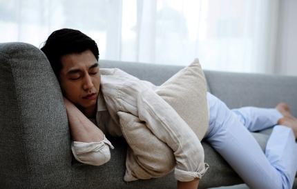 소파에 누워 낮잠을 자고 있는 남성