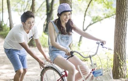 자전거를 타고 있는 여성과 뒤에서 잡아 주는 남성