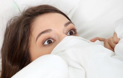 침대에 누워 깜짝 놀라는 여자
