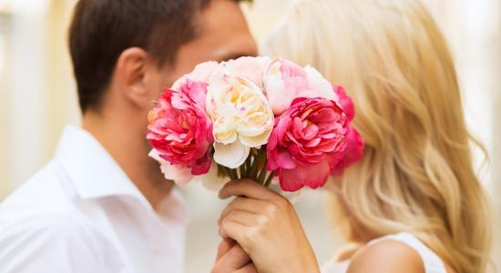 꽃으로 가리고 키스하는 연인