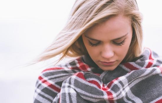 담요로 몸을 감싸고 있는 여자