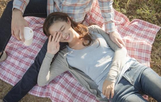 공원에서 남자의 다리를 베고 누운 여자