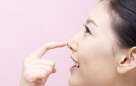 자신의 코를 만지는 여성