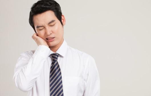 치아에 통증을 느끼는 남성