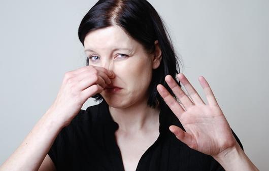 코를 막고 있는 여성