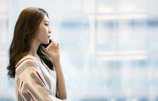 휴대전화기를 들고 있는 여성