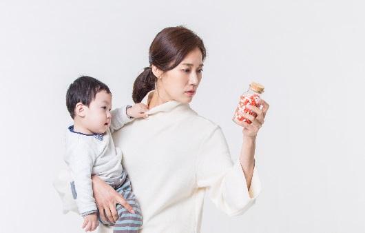 아이를 안고 약병을 확인하는 여성