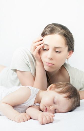 자고 있는 아이의 옆에 근심어린 표정의 여성