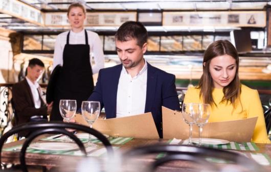 식당에서 메뉴를 고르는 커플